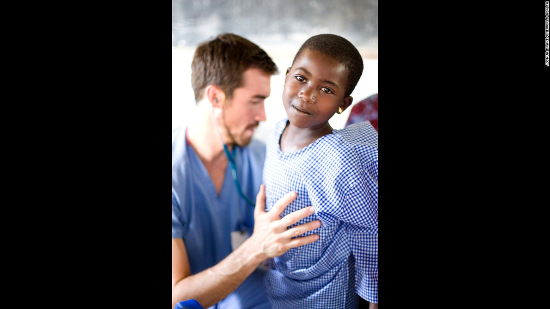 Dr. Cody Carpenter, a volunteer with OneWorld Health, checks on a patient during an outreach clinic in rural Uganda.