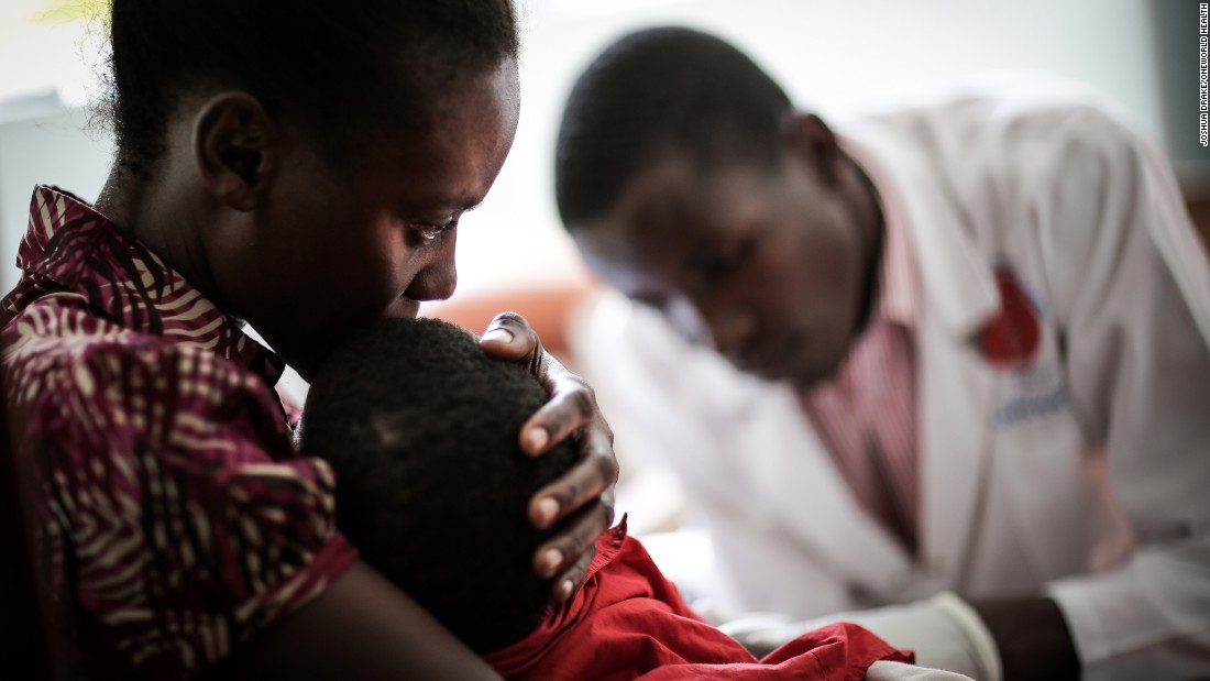 Nixon, a lab technician at the Masindi Kitara Medical Center, prepares to draw a sample from a young patient.
