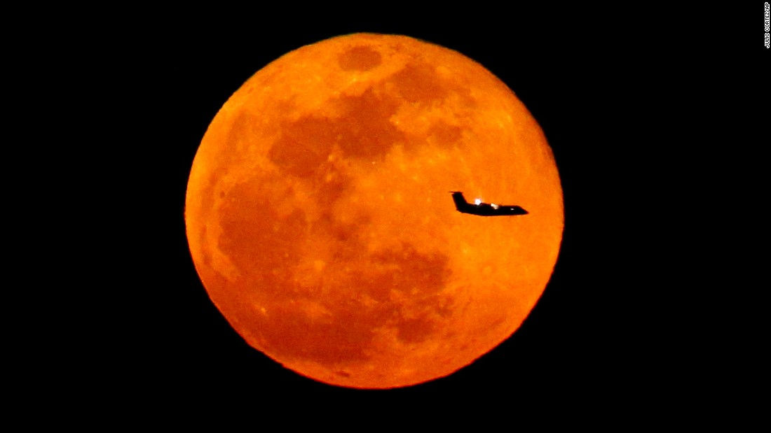 A full moon is the backdrop for a plane flying into Newark, New Jersey, on Wednesday, March 23.