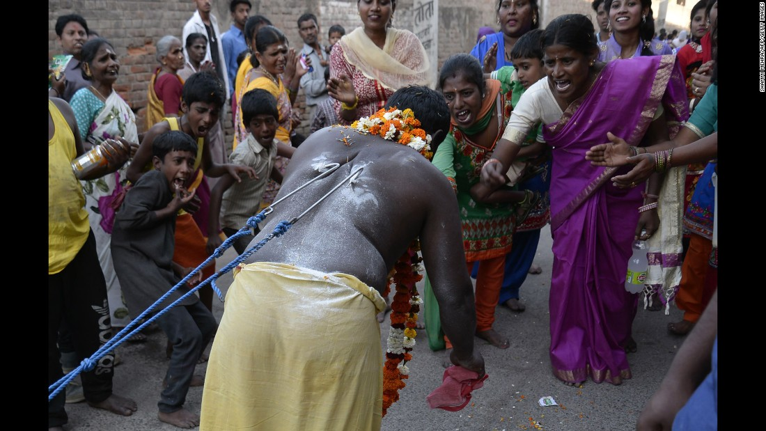 With hooks pierced through the skin of his back, a devotee of the Hindu god Murugan pulls a car during the Panguni Uthiram festival in Jalandhar, India, on Wednesday, March 23.