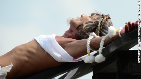 SAN FERNANDO, PAMPANGA - MARCH 25:  Participants hammer nails to the hand of Filipino Willy Salvador, 59 during a reenactment of Christ's suffering when he was nailed to the cross on Good Friday on March 25, 2016 in San Fernando town in Pampanga province, Philippines. The annual crucifixion and flagellation rites draws huge crowds of people to normally sleepy towns in northern Philippines.  (Photo by Dondi Tawatao/Getty Images)
