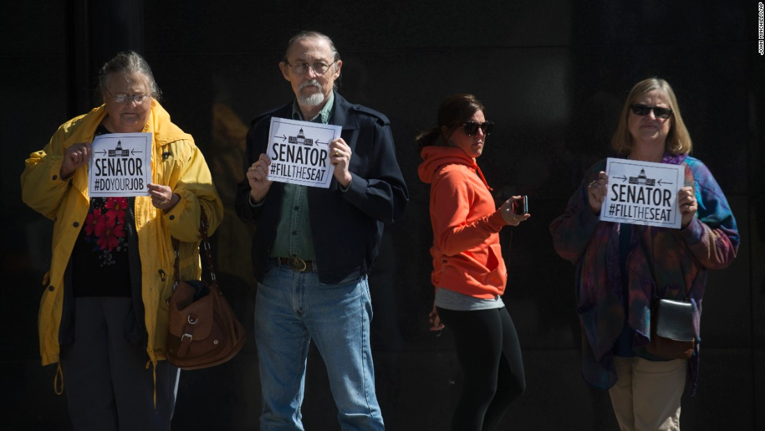 Demonstrators stand outside the office of U.S. Sen. Rob Portman, in Cincinnati, on Monday, March 21. A coalition of liberal groups staged rallies around the country on Monday targeting Republican senators who oppose confirmation hearings for President Barack Obama's Supreme Court nominee Merrick Garland.