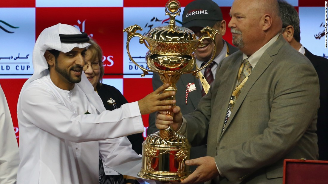 Sheikh Hamdan Bin Mohammad Bin Rashid al-Maktoum,  crown prince of Dubai, presents the owners of U.S. horse California Chrome with the Dubai World Cup trophy.