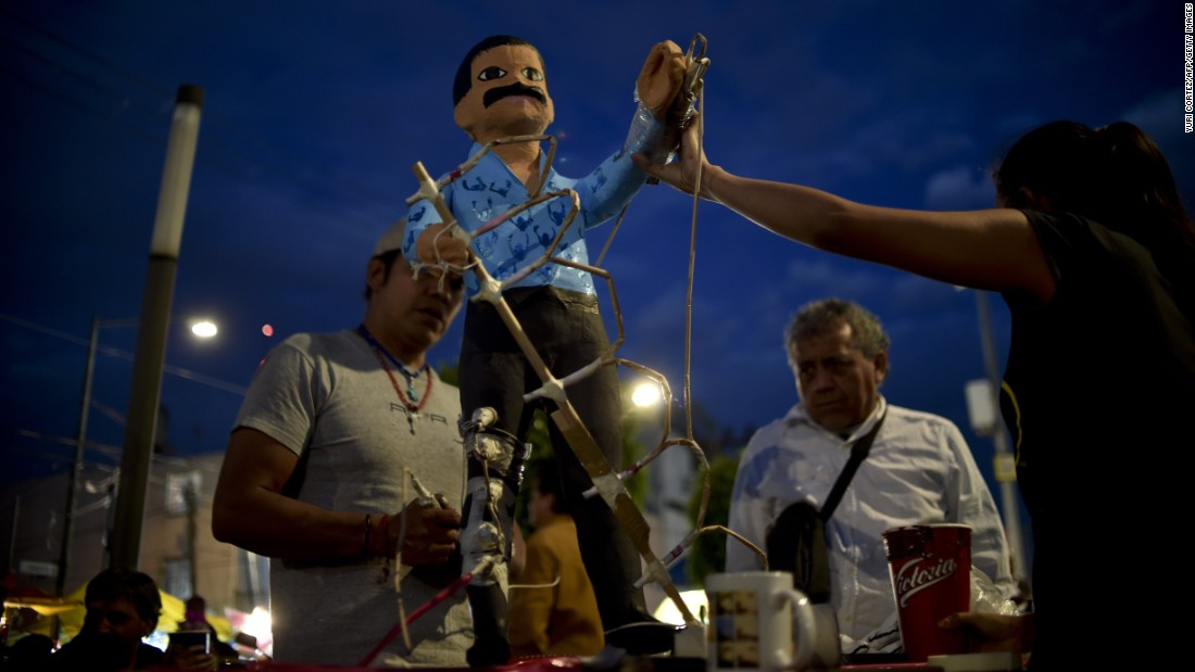 "Mexicans prepare to set fire to an effigy representing drug lord Joaquin ""El Chapo Guzman."""