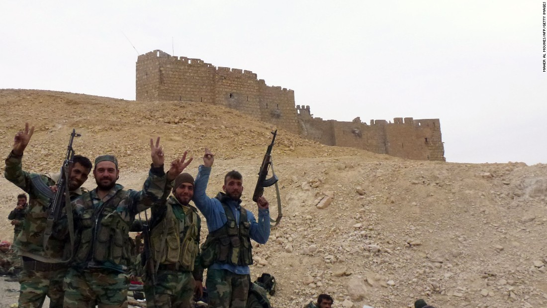 Syrian forces pose next to the Palmyra Castle on March 26.