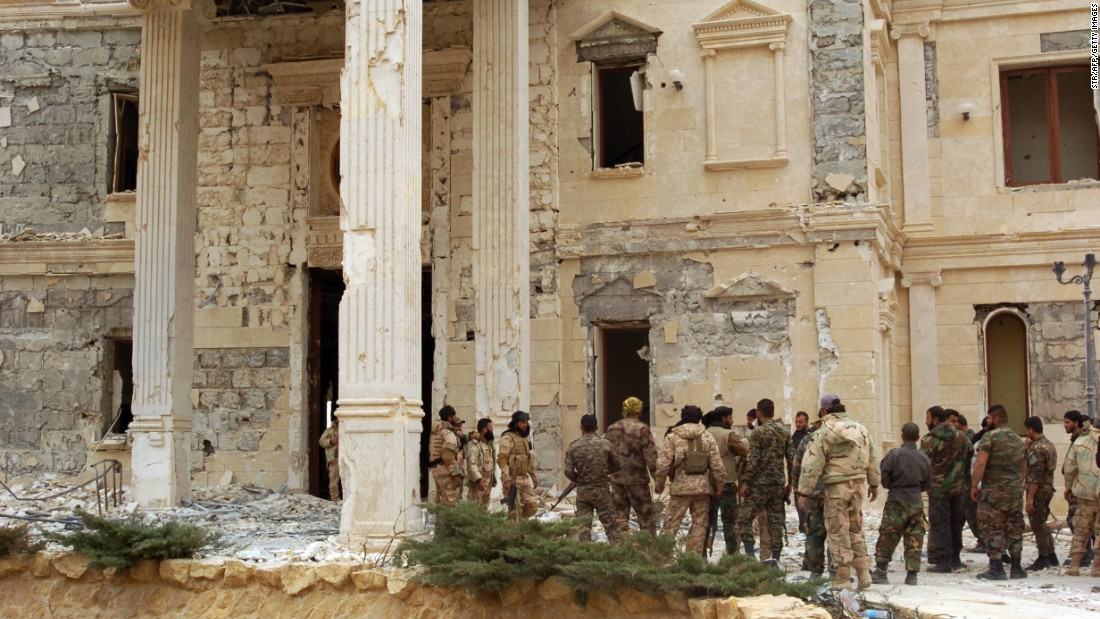 Syrian troops stand next to a mansion belonging to the Qatari royal family on March 24.