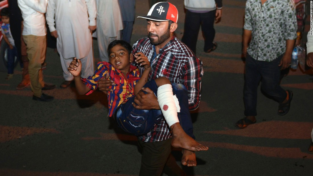 A man carries an injured child away from the scene of the blast.