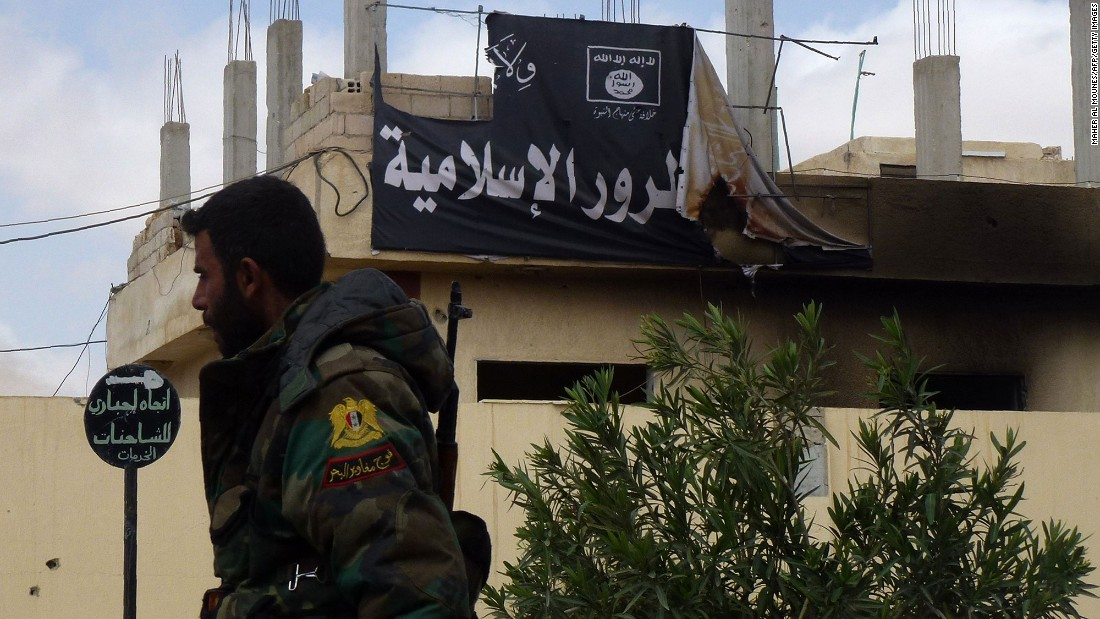 A member of the Syrian military walks past a banner bearing ISIS slogans on March 27.