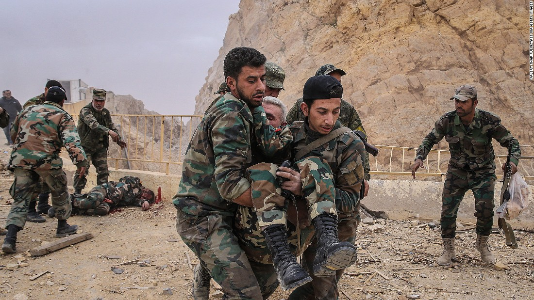 Syrian soldiers carry a wounded comrade after an explosion near the castle on Saturday, March 26.