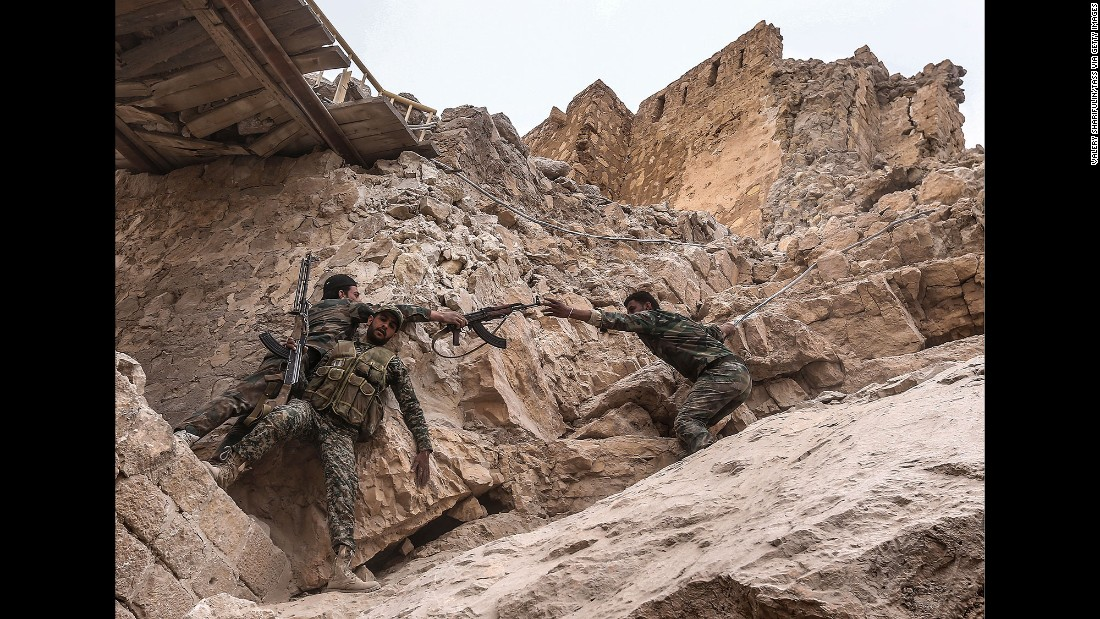 Syrian soldiers climb to the top of the castle to place a flag on March 26.