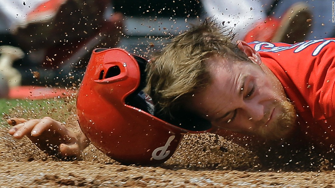 Philadelphia's Ryan Jackson hits the dirt near home plate during a spring-training game in Clearwater, Florida, on Saturday, March 26. He was tagged out on the play.