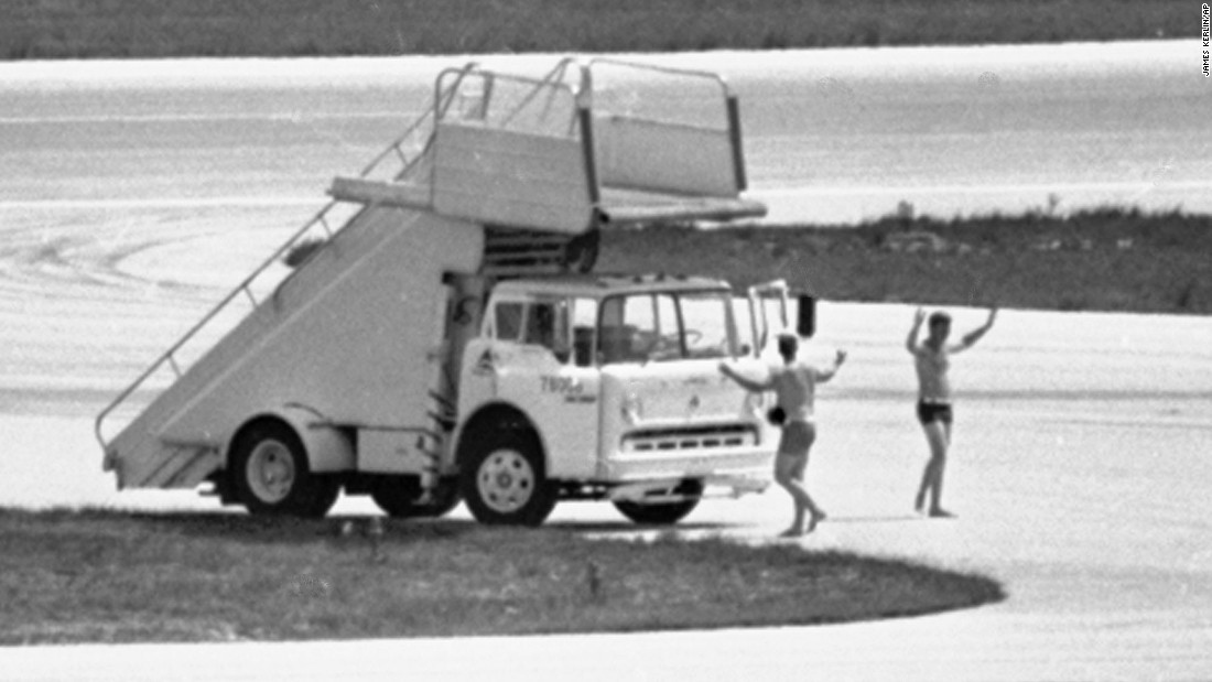 In this July 1972 photo, FBI agents in Miami, wearing only swim trunks, per a hijacker's instructions, prepare to deliver a case containing a $1 million ransom to a hijacked Delta DC-8 jet.