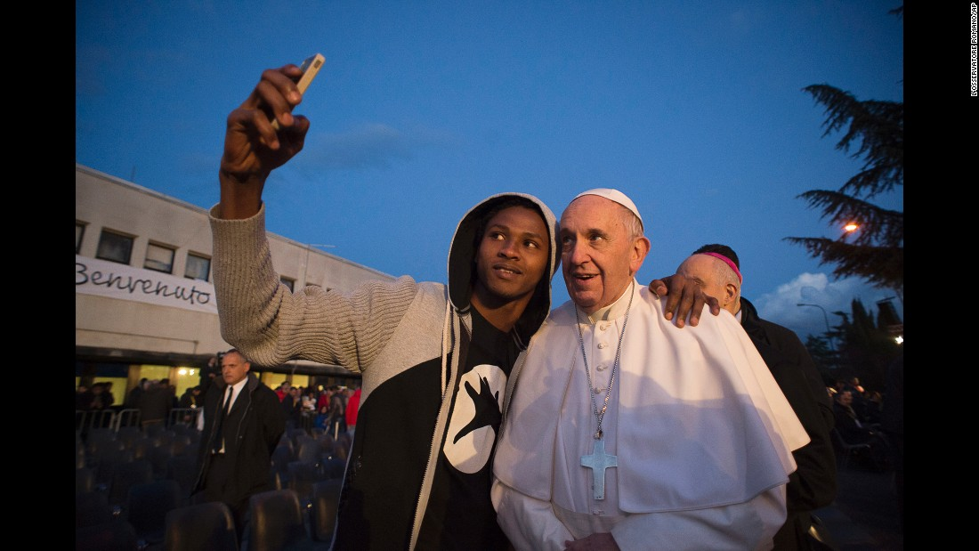 Pope Francis poses for a selfie during his visit to a refugee center in Rome on Thursday, March 24.