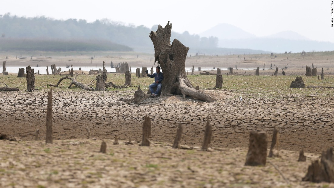 A villager in Thailand's Lampang Province takes a selfie at the dried-up Mae Chang reservoir on Saturday, March 12. Thailand is facing its worst drought in decades.