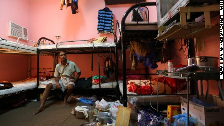 Kupttamon, an Indian laborer working in Qatar, sits in his room at a private camp housing foreign workers in Doha, on May 3, 2015.