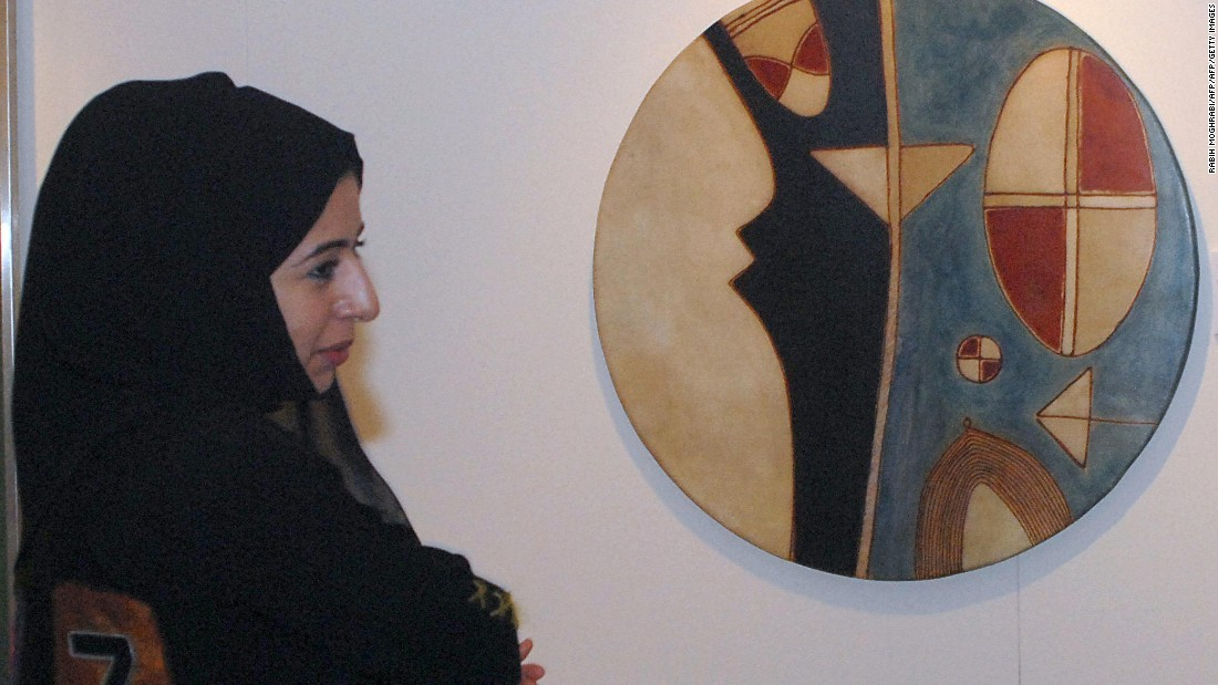 A woman is seen next to an art work by Farid Belkahia of Morocco before Christie's first public Modern and Contemporary art sale in the Middle East in 2006.