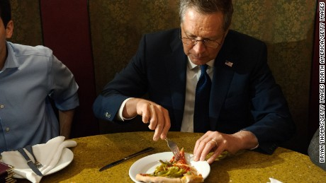 GOP Presidential Candidate John Kasich eats a piece of pizza at Gino's Pizzeria and Restaurant on March 30, 2016 in the Queens borough of New York City.