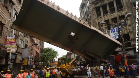Workers work on April 1 to remove a section of the collapsed overpass.