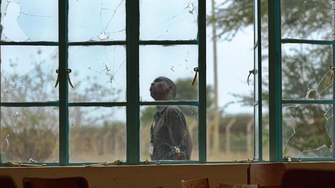 A man walks outside a lecture hall with bullet-shattered windowpanes. During the 2015 attack, the gunmen stormed in at dawn, separated Muslims and shot Christians to death. In some cases, the militants forced students to call relatives to listen in during the killings.<br />