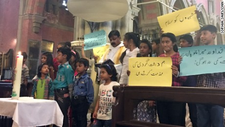 Children hold up placards condemning terrorism at a special service for the victims of the Gulshan Iqbal Park attack.