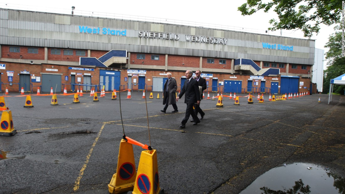 Coroner Lord Justice Goldring (centre) walks outside the Leppings Lane stand at Hillsborough as jurors examine the scene of the disaster. The cones show the layout of the area outside the ground as it had been in 1989.