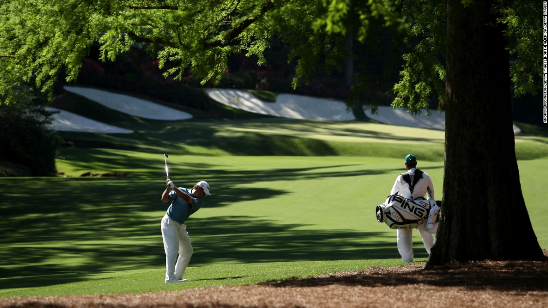 "Foster looks on as Westwood plays his second shot at the par 5 13th hole at Augusta National. ""It's a very demanding week, not only physically, because the elevation changes are so severe, but it's the most mentally demanding golf course we play all season. You can't switch off for one second or it will make you look stupid."""