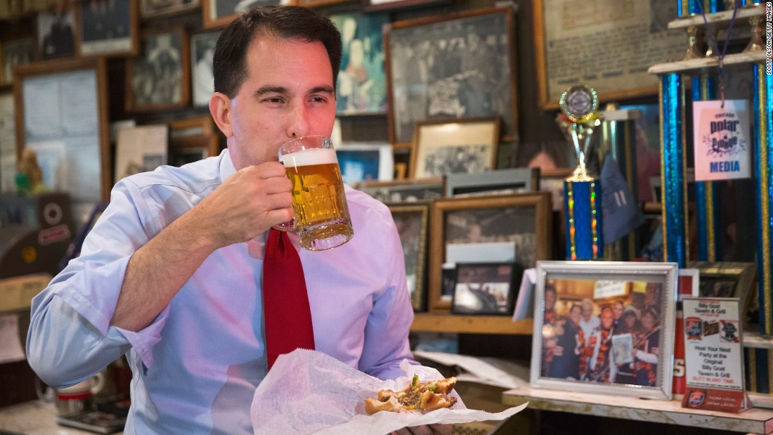 "Wisconsin Gov. Scott Walker washes down a ""cheezborger"" with a Schlitz beer at Chicago's Billy Goat Tavern in July."