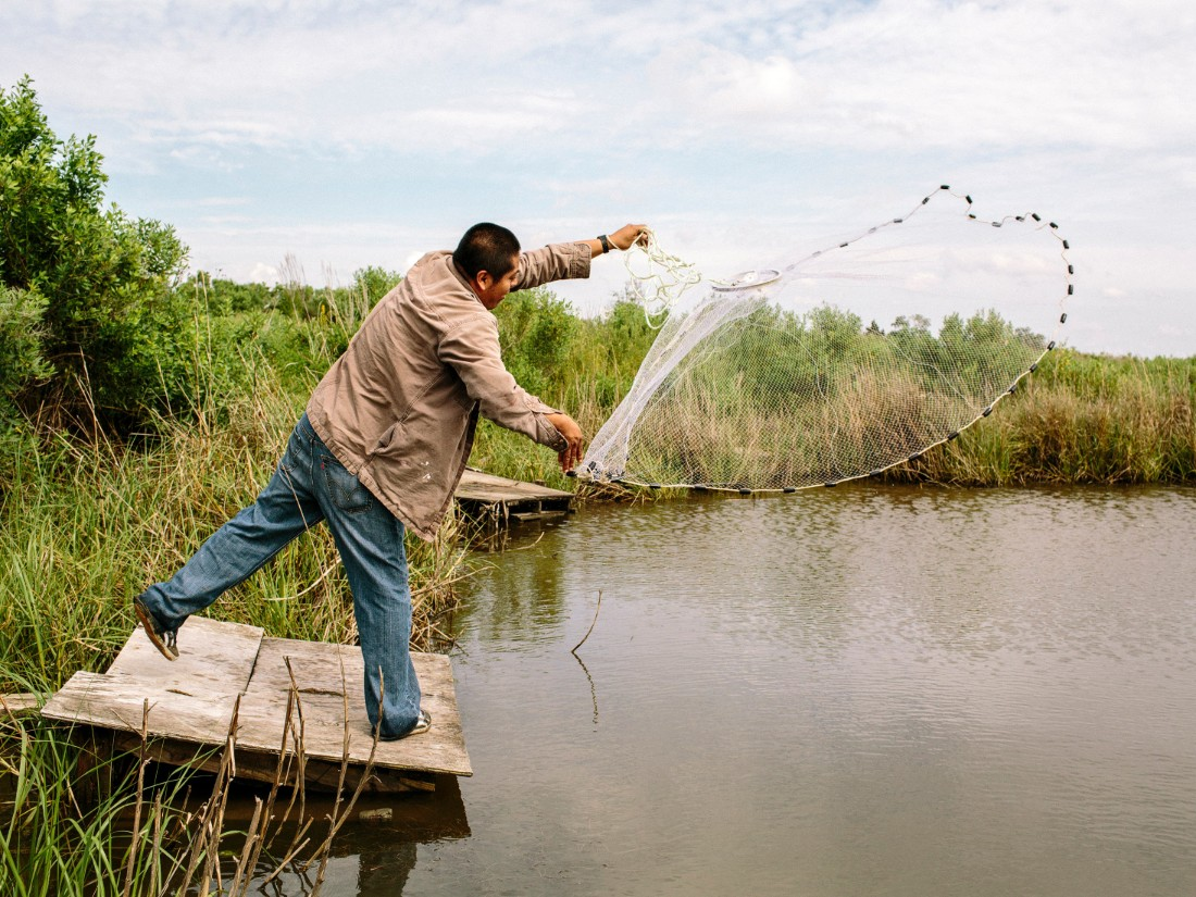 George Hernandez throws a cast net at the entrance to Isle de Jean Charles. Hernandez is a resident of nearby Houma, Louisiana, and he often travels to the island to fish. It's about 1.5 hours by car south of New Orleans.