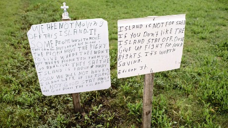 "Not everyone wants to leave the island. ""Some people want to move. They can go,"" says a handwritten sign posted beside Island Road. ""But leave us alone."""