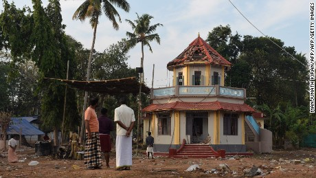 Indian bystanders gather in front of a damaged building at The Puttingal Devi Temple in Paravur some 60kms north-west of Thiruvananthapuram on April 11, 2016.  More than 100 people have died and 350 injured when fireworks meant to be lit for festivities caught fire and exploded near the temple where thousands of people had gathered to witness the festivities on the early hours of April 10.