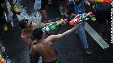 "People take part in water battles as they celebrate Songkran - the Thai new year - in Bangkok on April 13, 2016. Thais and tourists took to the streets on April 13 to drench each other in the mass water fight that marks the country's new year festival Songkran, as authorities attempted to crack down on alcohol, topless dancers and other ""indecencies""."