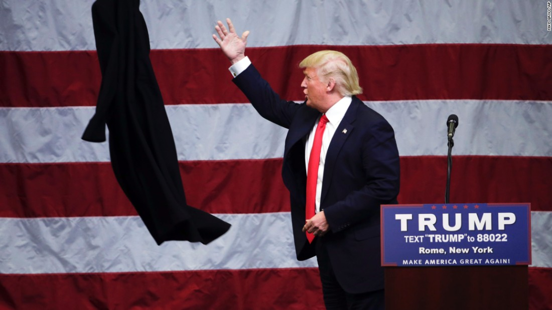 Republican presidential candidate Donald Trump tosses his coat during a rally in Rome, New York, on Tuesday, April 12.