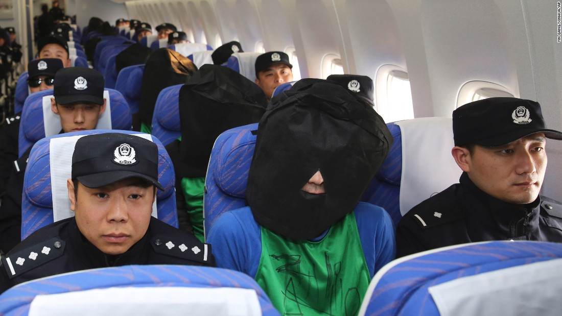 Suspects accused of wire fraud are guarded on a plane as they arrive in Beijing on Wednesday, April 13.