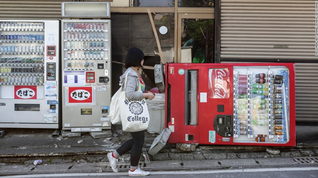 A resident passes by a toppled vending machine in Kumamoto on April 15.