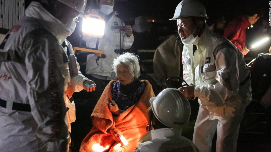 Rescue workers take care of a woman suffering from shock  at the evacuation center at the Mashiki Town Gymnasium on Saturday, April 16, in Kumamoto, Japan.