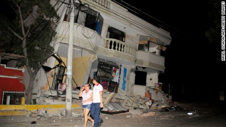 Residents walk on a street amid destroyed buildings on April 16, in Guayaquil, Ecuador.
