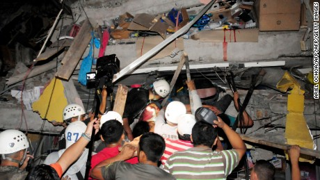 Rescue workers work to pull out survivors trapped in a collapsed building after a huge earthquake struck, in the city of Manta early on April 17, 2016.  At least 41 people were killed when a powerful 7.8-magnitude earthquake struck Ecuador, destroying buildings and sending terrified residents dashing from their homes, authorities said late on April 16.  / AFP / API / ARIEL OCHOA        (Photo credit should read ARIEL OCHOA/AFP/Getty Images)