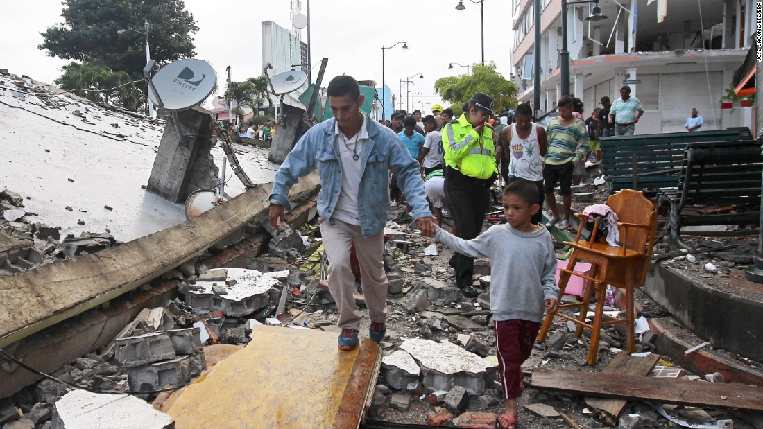 People make their way through debris from a collapsed building in Pedernales, Ecuador, on April 17.