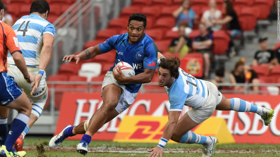 Samoa's Tomasi Alosio (C) runs past Argentina during their Cup quarter-final match at the Singapore Sevens rugby tournament on April 17, 2016.