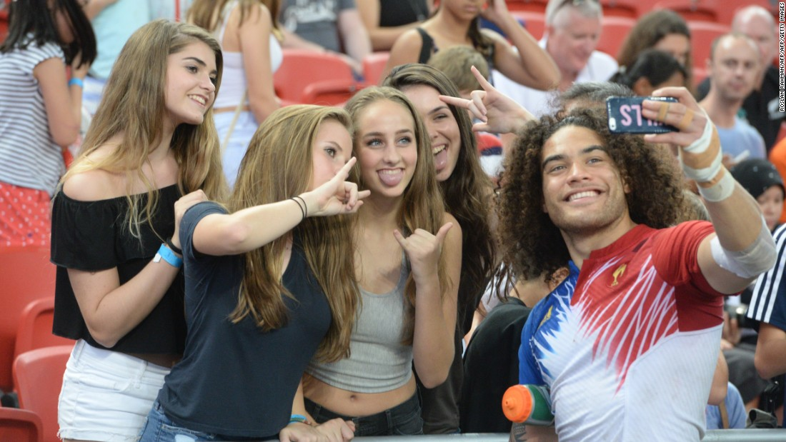 France's Pierre Gilles Lakafia (R) takes a selfie with fans during the Singapore Sevens rugby tournament on April 17, 2016.