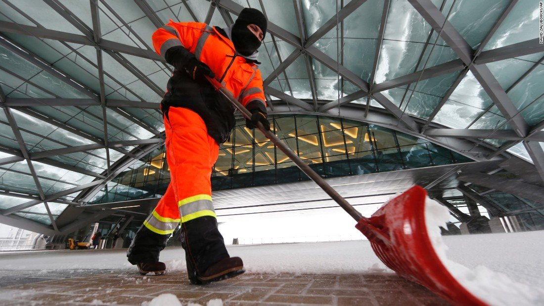 Joseph Dominguez uses a shovel to clear snow between the main terminal of Denver International Airport and the adjoining hotel on Saturday, April 16, in Denver.