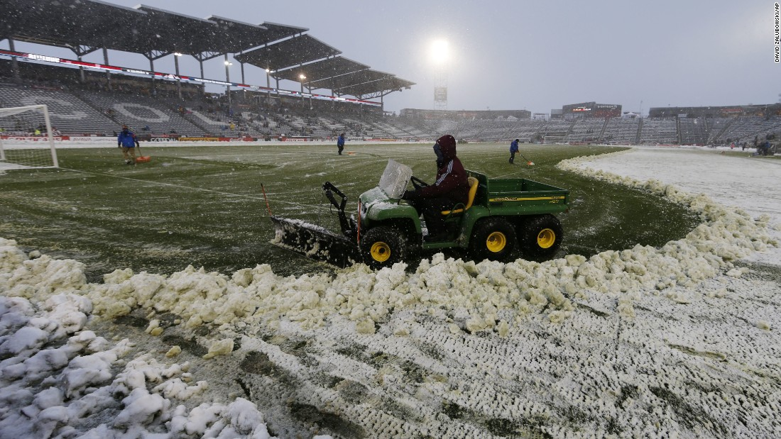 Maintenance workers use tractors to plow the pitch before the Colorado Rapids were to host the New York Red Bulls in an MLS soccer match on April 16 in Commerce City, Colorado.