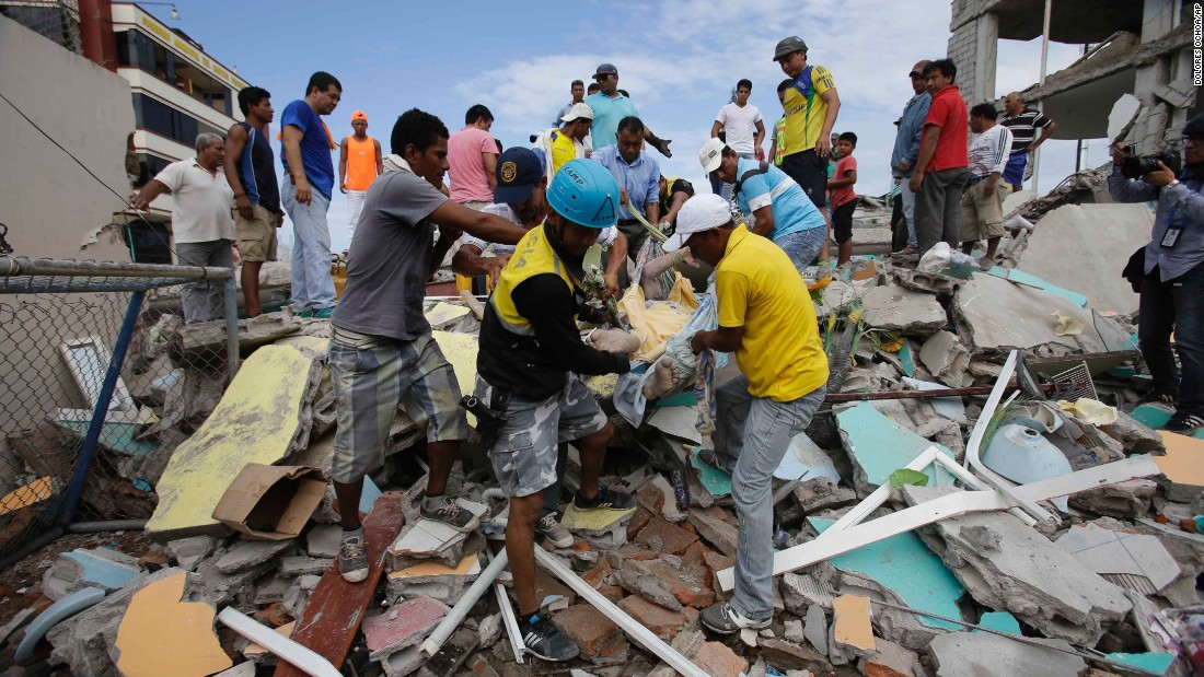 Volunteers remove a body from a destroyed house  in Pedernales, Ecuador, on April 17.