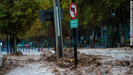 View of a flooded street due to the overflowing of the Mapocho river during heavy rains in Santiago on April 17, 2016. Four million people in Santiago were without tap water Sunday after unusually heavy rain pounding central Chile triggered landslides that fouled the city's water supply and forced the closure of the world's biggest copper mine, officials said. / AFP / MARTiN BERNETTi        (Photo credit should read MARTIN BERNETTI/AFP/Getty Images)