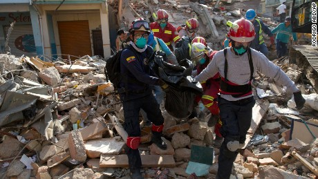Firefighters remove a body recovered from a destroyed building in Portoviejo, Ecuador, Monday, April 18, 2016.