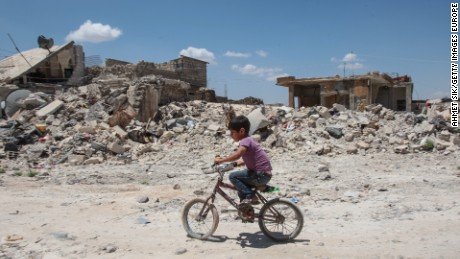 TAL ABYAD, SYRIA - JUNE 20: (TURKEY OUT) A boy rides his cycles in the streets of the destroyed Syrian town of Kobane, also known as Ain al-Arab, Syria. June 20, 2015. Kurdish fighters with the YPG took full control of Kobane and strategic city of Tal Abyad, dealing a major blow to the Islamic State group's ability to wage war in Syria. Mopping up operations have started to make the town safe for the return of residents from Turkey, after more than a year of Islamic State militants holding control of the town. (Photo by Ahmet Sik/Getty Images)
