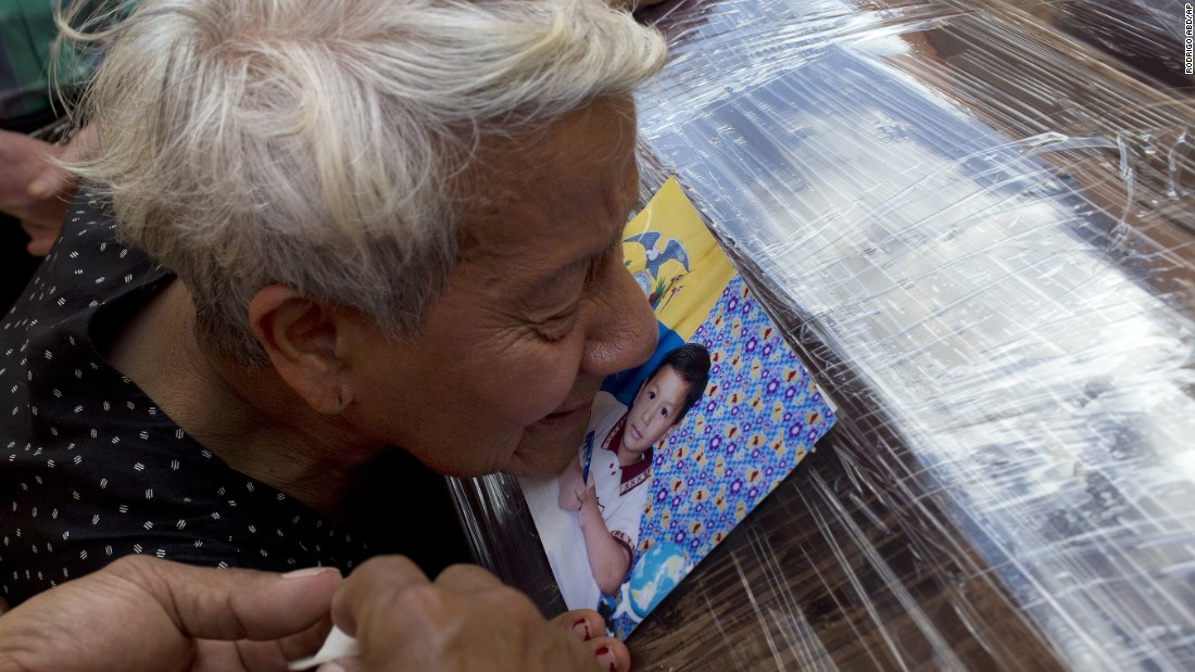 A relative kisses a photo of Kexly Valentino attached to her coffin in Montecristi on April 19. Kexly and her mother and brother died in the quake.