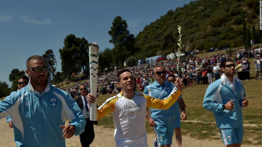 The first torchbearer was Greek gymnastics world champion Eleftherios Petrounias. The torch is beginning a six-day relay tour of Greece which includes a pass through a refugee camp in Athens.