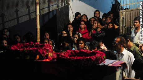 Pakistani relatives look at the coffin of a policeman who was killed with other colleagues in an attack by gunmen during his funeral in Karachi on April 20, 2016.