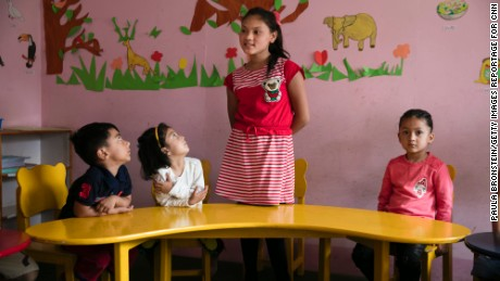 Maya recites phrases in English in her kindergarten. She will soon turn 11  and hopes to catch up to children her age.